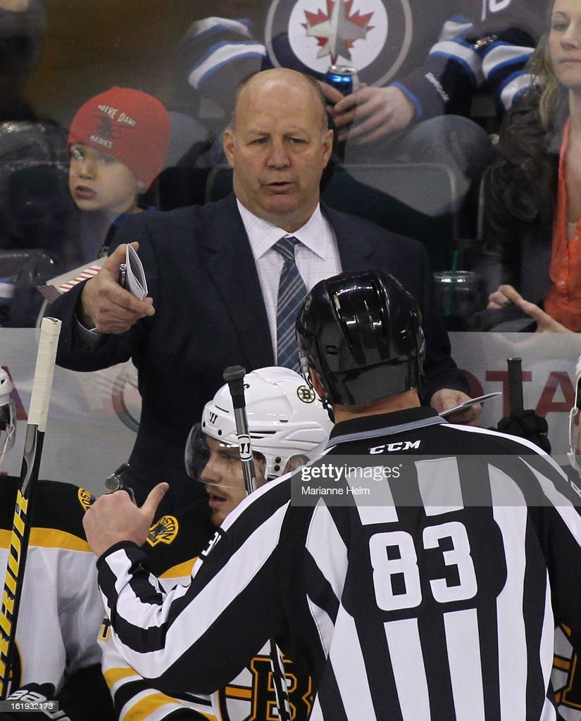 Boston Bruins' head coach Claude Julien speaks with linesman Matt MacPherson #83 from the bench during a game against the Winnipeg Jets on February 17, 2013 at the MTS Centre in Winnipeg, Manitoba, Canada.