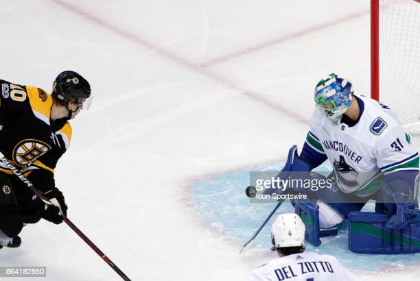 Boston Bruins left wing Anders Bjork eyes the loose puck and his first goal of the game during a game between the Boston Bruins and the Vancouver...