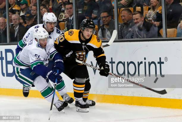 Boston Bruins left wing Anders Bjork flips the puck to the point chased by Vancouver Canucks defenseman Derrick Pouliot and Vancouver Canucks...