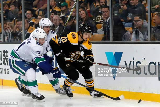 Boston Bruins left wing Anders Bjork pressured by Vancouver Canucks defenseman Troy Stecher and Vancouver Canucks defenseman Derrick Pouliot during a...