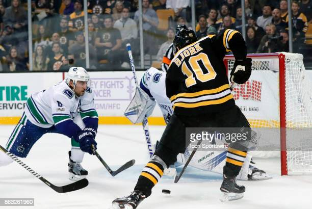 Boston Bruins left wing Anders Bjork tries to get the handle on a hat trick bid as Vancouver Canucks defenseman Chris Tanev moves in during a game...