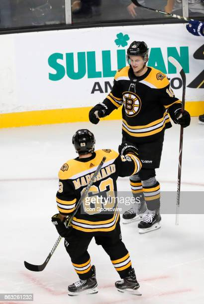 Boston Bruins left wing Brad Marchand congratulates Boston Bruins left wing Anders Bjork on the first of his two goals during a game between the...