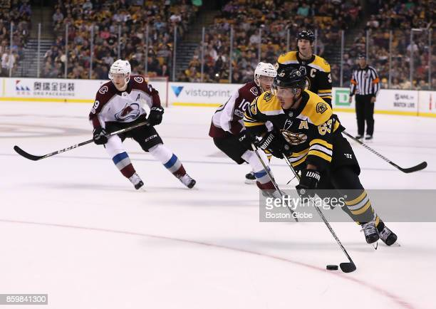 Boston Bruins left wing Brad Marchand skates with the puck in front of Colorado Avalanche center Nathan MacKinnon and right wing Sven Andrighetto...