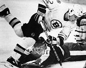 Boston Bruins player Randy Burridge top jumps over Toronto Maple Leafs goaltender Ken Wregget bottom in the first period of a game at the Boston...