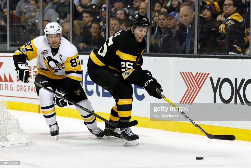 Boston Bruins right defenseman Brandon Carlo (25) moves for the puck with Pittsburgh Penguins center Sidney Crosby (87) close by during a regular season NHL game between the Boston Bruins and the Pittsburgh Penguins on January 26, 2017 at TD Garden in Boston, Massachusetts. The Bruins defeated the Penguins 4-3.