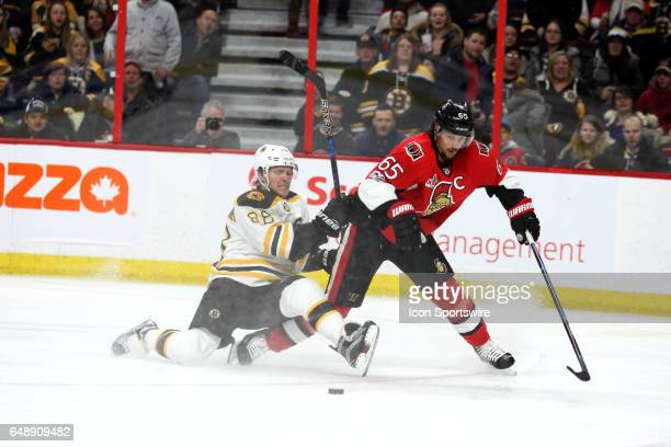 Boston Bruins Right Wing David Pastrnak gets tangled up as Ottawa Senators Defenceman Erik Karlsson strips him off the puck during the second period...