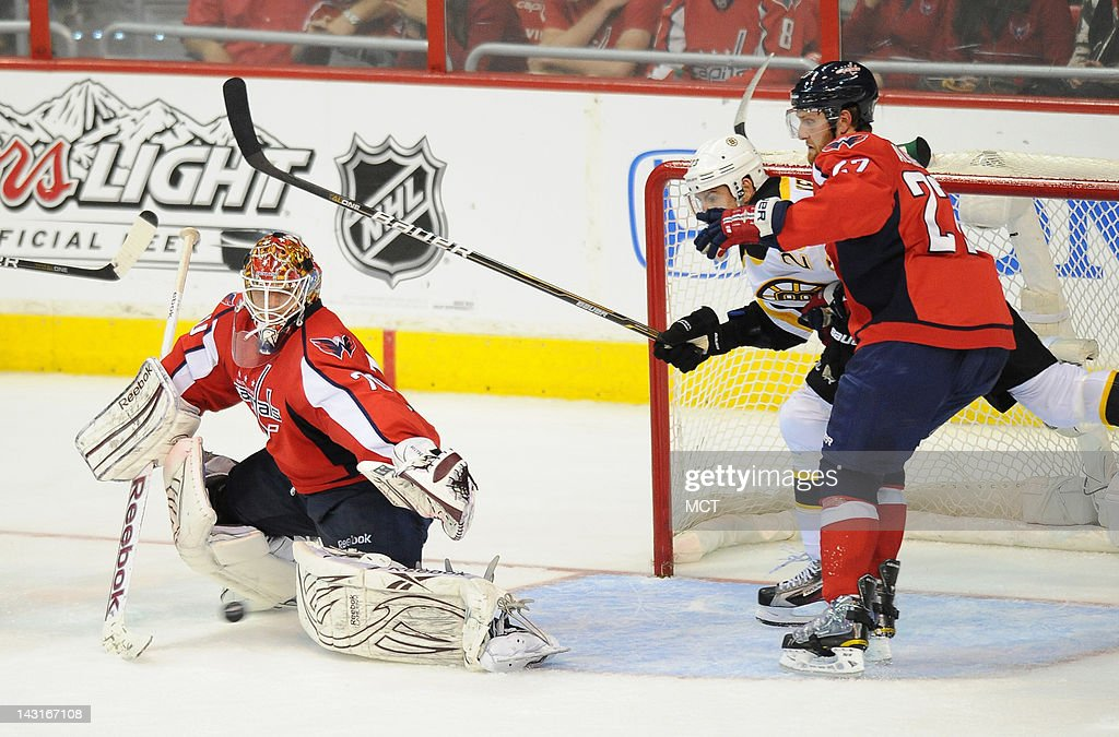A Boston Bruins shot whistles past Washington Capitals goalie Braden Holtby (70), as Capitals defenseman Karl Alzner (27) blocks Bruins center Chris Kelly (23), in the third period of Game 4 of the NHL Eastern Conference quarterfinals at the Verizon Center in Washington, D.C., Thursday, April 19, 2012. The Capitals defeated the Bruins, 2-1.