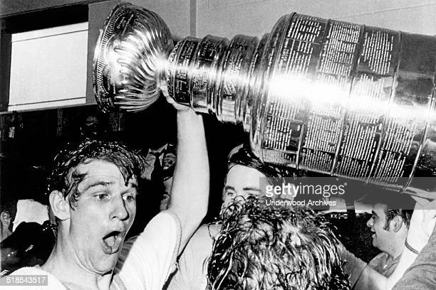 Boston Bruins star Bobby Orr whoops and holds up the Stanley Cup after he scored the winning goal in overtime against the St Louis Blues at the...