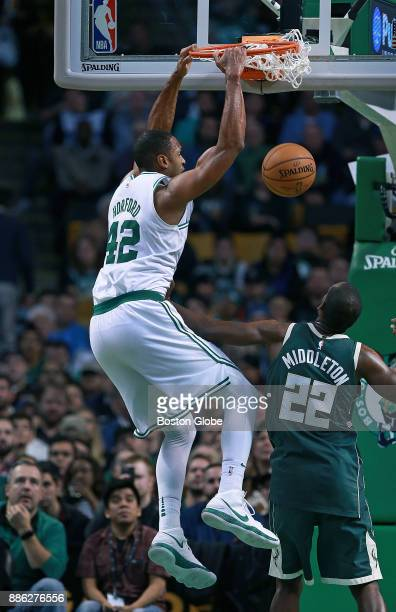 Boston Celtics' Al Horford makes the third of his three consecutive slam dunks in the fourth quarter this one over the Bucks' Khris Middleton The...