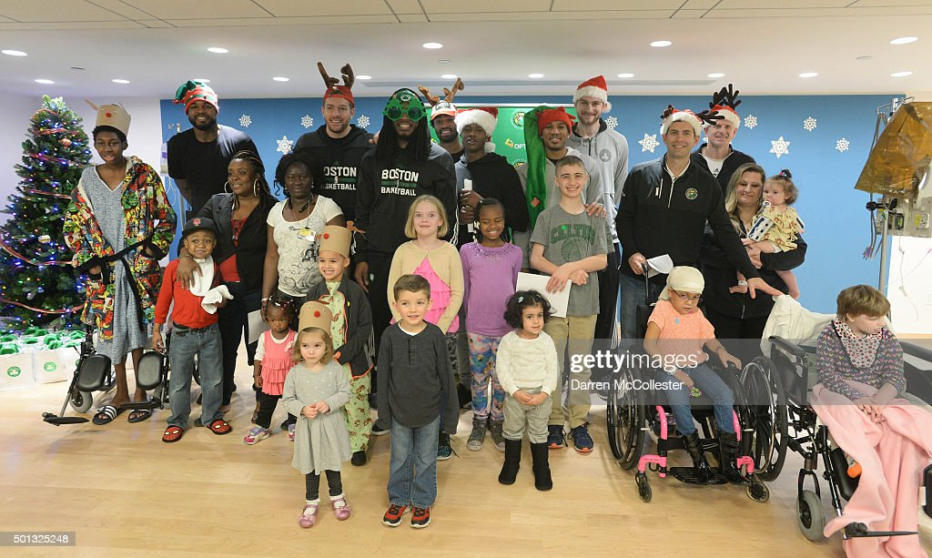Boston Celtics (L to R) Amir Johnson, David Lee, Jae Crowder, James Young, Terry Rozier, Avery Bradley, Tyler Zeller, head coach Brad Stevens, and assistant coach Jay Larranaga pose for a picture with the kids at Boston Children's Hospital December 14, 2015 in Boston, Massachusetts.