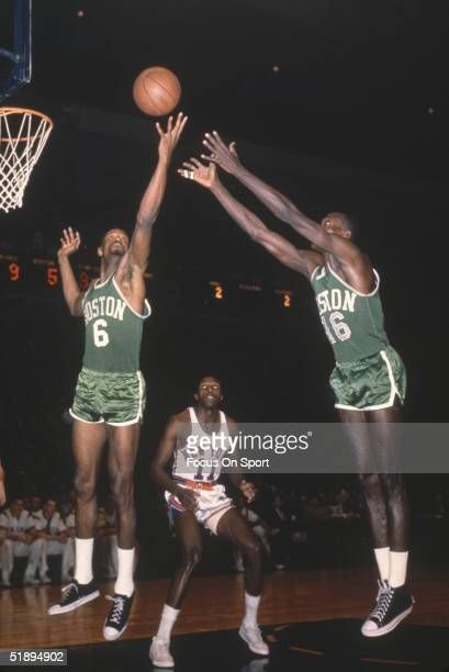 Boston Celtics' Bill Russell and Tom Sanders jump to grab a rebound against the New York Knicks' Johnny Greene at Madison Square Garden in New York...