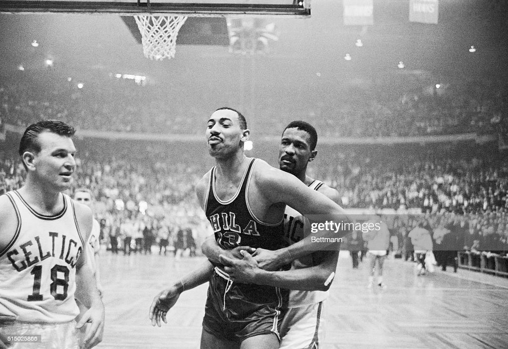 Celtics' Bill Russell pins Warriors' Wilt Chamberlain's right arm and holds him during wild 4th quarter in which both sides fought Boston won game...
