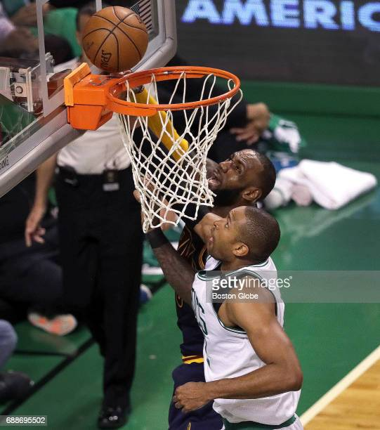 Boston Celtics center Al Horford puts up a shot as he drives by Cleveland Cavaliers forward LeBron James for a second effort putback during the...