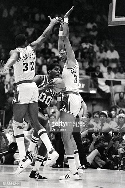 Boston Celtics center Robert Parrish squeezes through a double team of Los Angeles Lakers guard Magic Johnson and center Kareem AbdulJabbar in the...