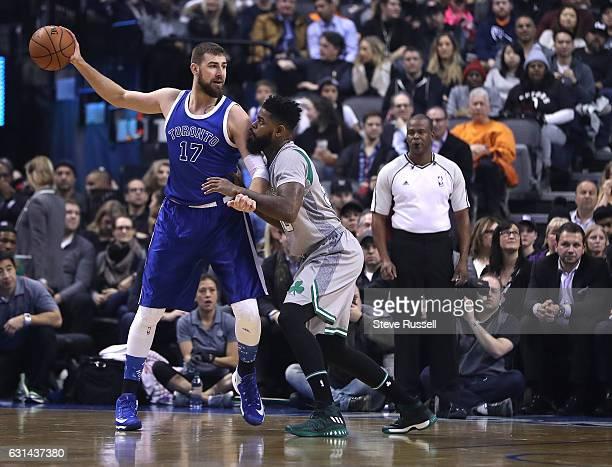 TORONTO ON JANUARY 10 Boston Celtics forward Amir Johnson defends against Toronto Raptors center Jonas Valanciunas as the Toronto Raptors wearing...