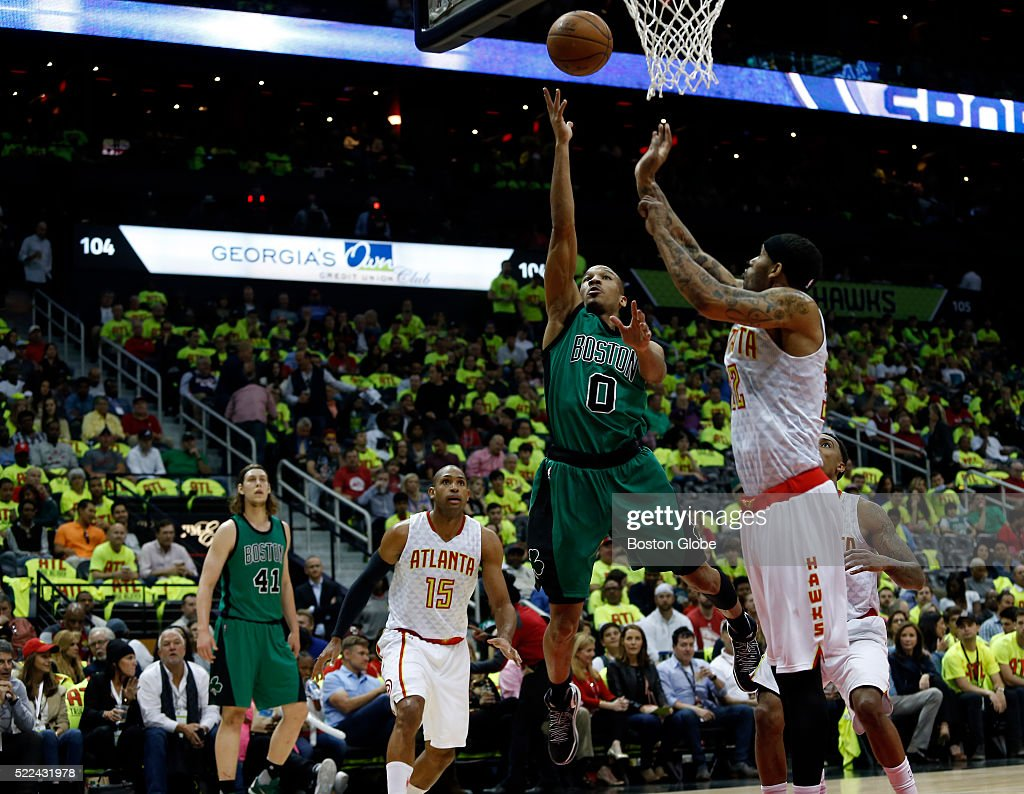 Boston Celtics guard Avery Bradley center shoots against Atlanta Hawks forward Mike Scott right during the second quarter of Game 1 in the first...