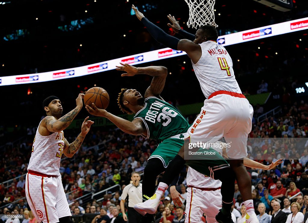 Boston Celtics guard Marcus Smart center falls back as he drives to the basket between Atlanta Hawks forwards Mike Scott left and Paul Millsap during...