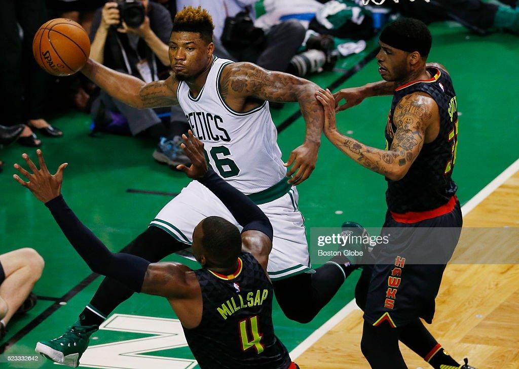 Boston Celtics guard Marcus Smart passes under the net between Atlanta Hawks players Paul Millsap bottom and Mike Scott during the third quarter of...