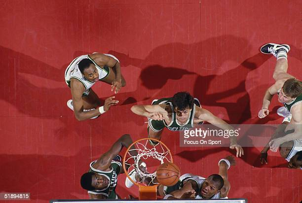Boston Celtics Kevin McHale watches his shot as his teammates and Milwaukee Bucks players jump to catch the rebound at the basket during a game circa...