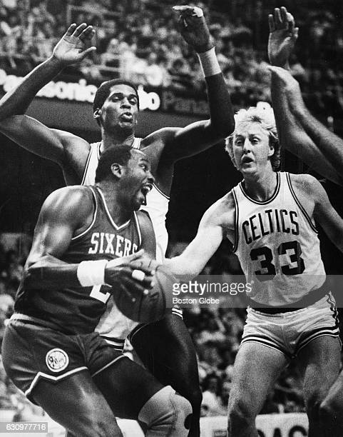 Boston Celtics' Larry Bird right fights for the ball against Philadelphia 76ers' Moses Malone during an NBA game at the Boston Garden in Boston on...