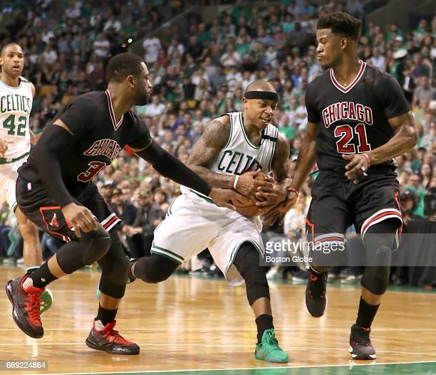 Boston Celtics player Isaiah Thomas runs into defensive pressure from Chicago Bulls players Dwayne Wade and Jimmy Butler during second quarter action...