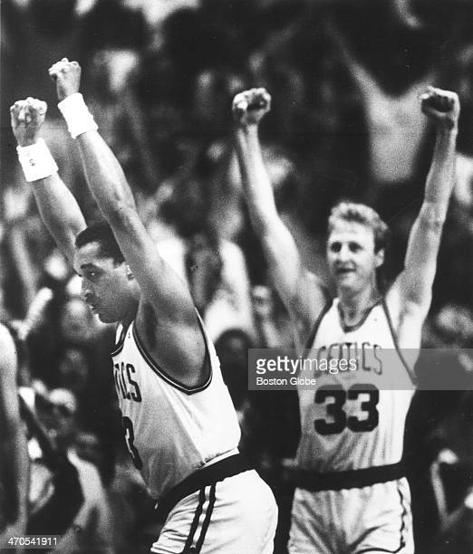 Boston Celtics players Dennis Johnson and Larry Bird raise their hands in victory after Bird stole the ball passing to Johnson who scored the winning...