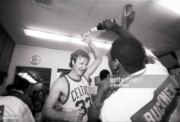 Boston Celtics players Larry Bird and Quinn Buckner celebrate the team's NBA championship in the locker room after Game 7 of the NBA Finals outside...