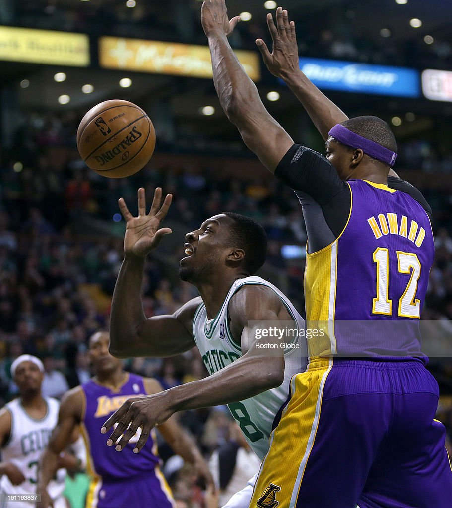 Boston Celtics power forward Jeff Green (#8) briefly lost control of the ball while being defended by Los Angeles Lakers center Dwight Howard (#12) but recovered possession scoring over Howard with a nice reverse hook shot during the first quarter as the Boston Celtics play the Los Angeles Lakers at TD Garden.