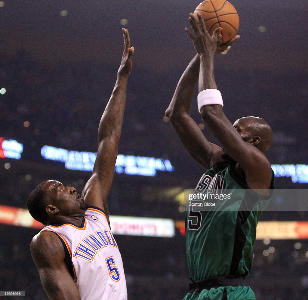 Boston Celtics power forward Kevin Garnett (#5) drains a short jumper over old friend and former teammate Oklahoma City Thunder center Kendrick Perkins (#5) during the first quarter as the Celtics play the Oklahoma City Thunder at TD Garden.