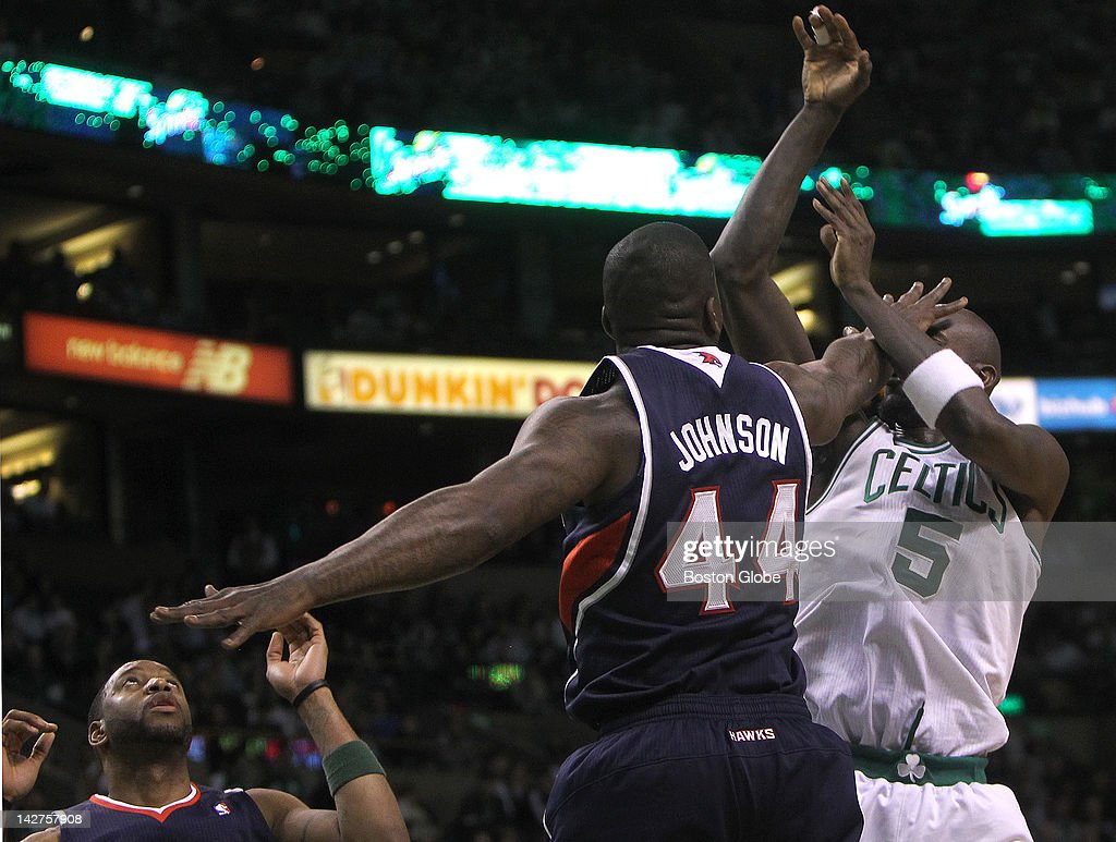 Boston Celtics power forward Kevin Garnett (#5) gets a shot off despite the hand in the face from Atlanta Hawks forward Ivan Johnson (#44) during the first half. Boston Celtics NBA basketball, action and reaction. The Boston Celtics took on the Atlanta Hawks at TD Garden.