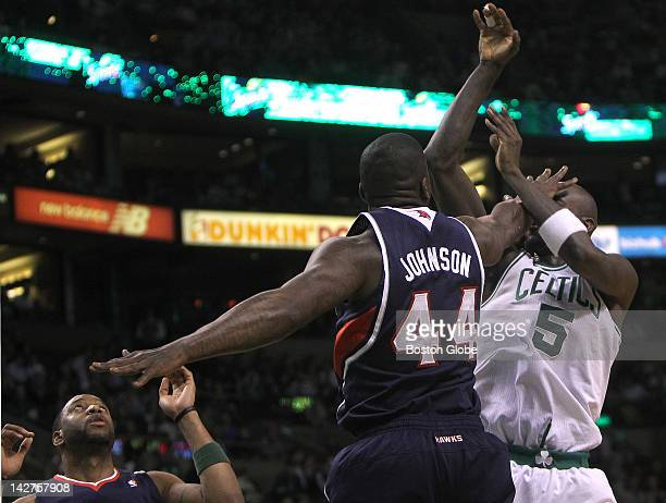 Boston Celtics power forward Kevin Garnett gets a shot off despite the hand in the face from Atlanta Hawks forward Ivan Johnson during the first half...