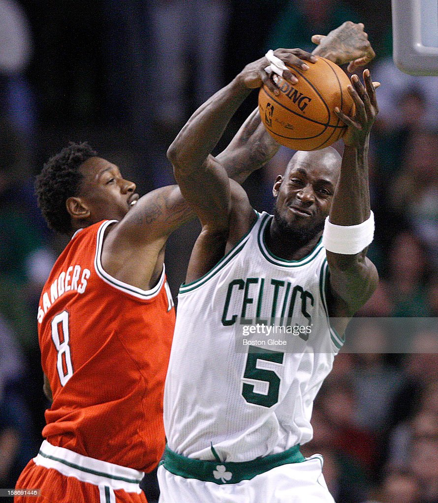 Boston Celtics power forward Kevin Garnett (#5) outmuscles Milwaukee Bucks center Larry Sanders (#8) for the ball during the first half as the Celtics play the Milwaukee Bucks at TD Garden.