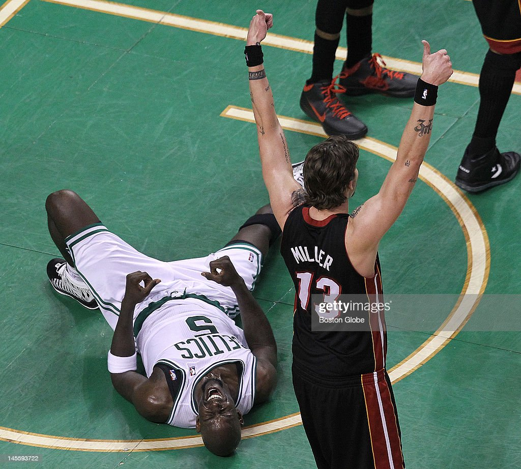 Boston Celtics power forward Kevin Garnett (#5) writhes in agony on the parquet after being thrown to the ground battling for a loose ball. Miami Heat shooting guard Mike Miller (#13) signals jump ball. Boston Celtics NBA basketball, action and reaction. The Celtics play the Miami Heat in game three of the Eastern Conference Finals at TD Garden.