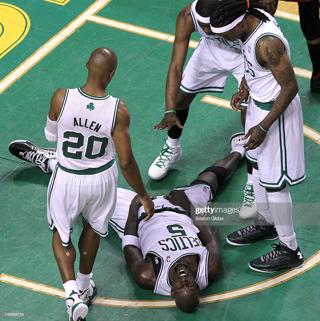 Boston Celtics power forward Kevin Garnett (#5) writhes in agony on the parquet after being thrown to the ground battling for a loose ball. Boston Celtics NBA basketball, action and reaction. The Celtics play the Miami Heat in game three of the Eastern Conference Finals at TD Garden.