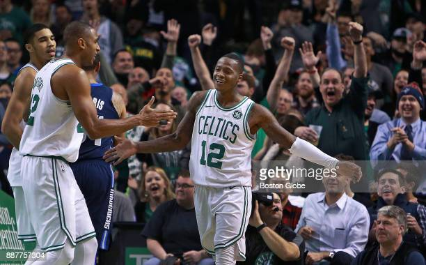 Boston Celtics' Terry Rozier brings the crowd out of their seats and gets a hand from teammate Al Horford left after taking a nearly fullcourt pass...
