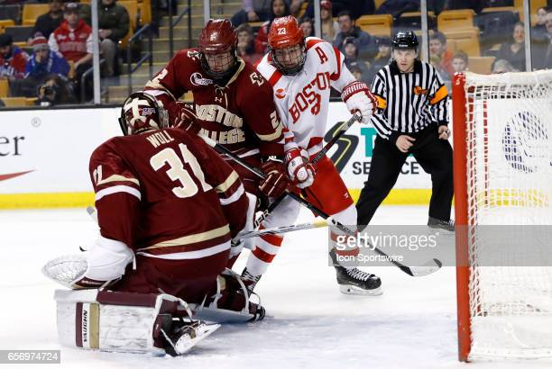 Boston College Eagles defenseman Scott Savage keeps Boston University Terriers forward Jakob Forsbacka Karlsson from the puck in front of Boston...