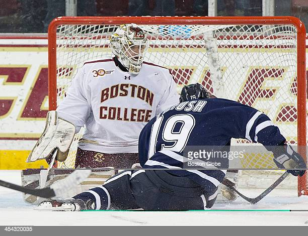 Boston College Eagles goalie Brian Billett blocks the shot and University of New Hampshire Wildcats men's ice hockey player Casey Thrush during first...