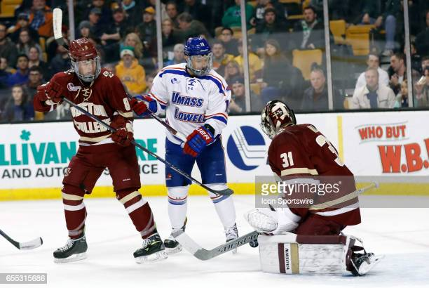 Boston College Eagles goaltender Joseph Woll gets enough of the puck with Boston College Eagles defenseman Jesper Mattila and UMass Lowell River...
