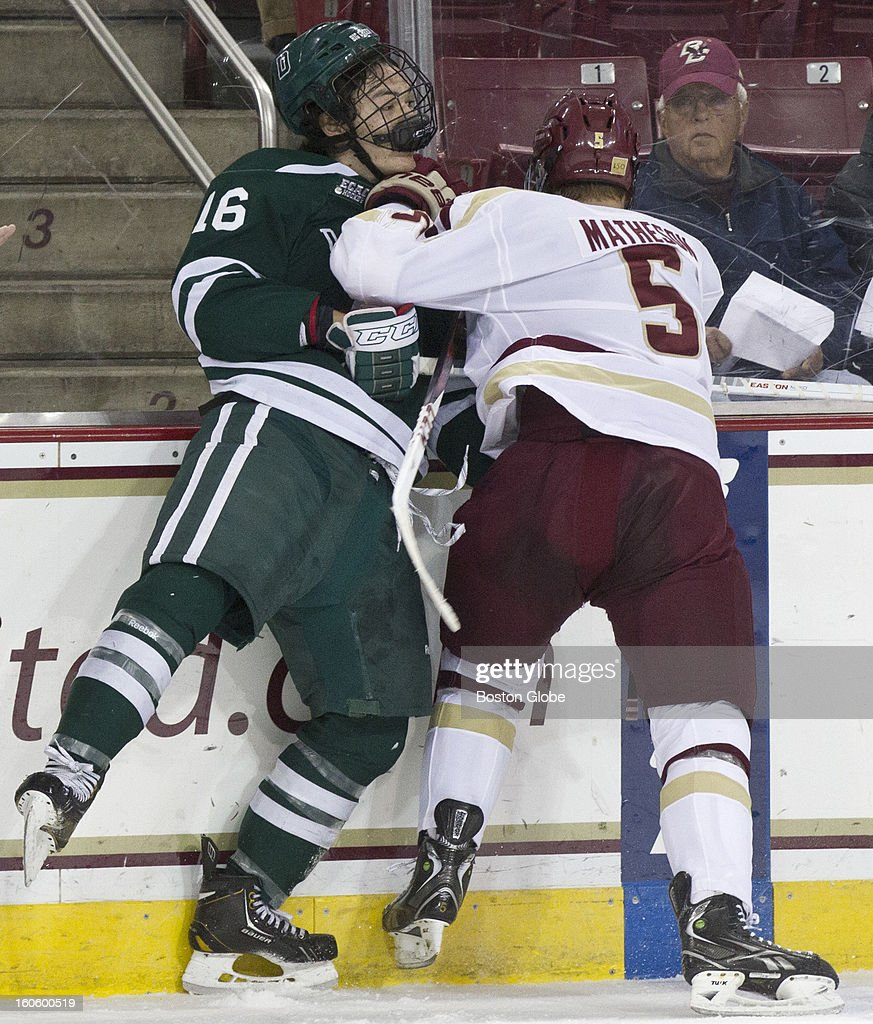 Boston College Eagles Michael Matheson checks Dartmouth Big Green Tyler Sikura into the boards during 1st period action at Kelley Rink in Conte Forum on Saturday, Nov. 22, 2012.