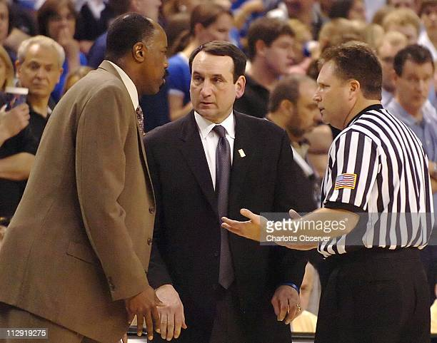 Boston College head coach Al Skinner left and Duke head coach Mike Krzyzewski talk with an official about the penalties issued following a skirmish...