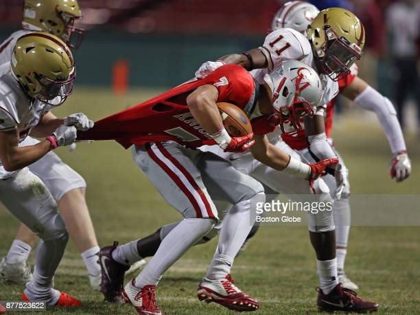Boston College High's Bobby DeMeo left stretches the jersey of Catholic Memorial's Hunter Tully as he and teammate Kaleb Moody bring him down in the...