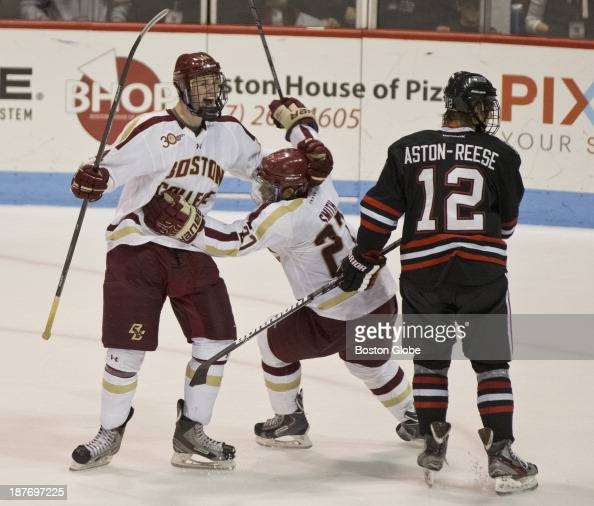 Boston College hockey player Adam Gilmour celebrates his game winning goal with teammate Quinn Smith in front of Northeastern University's Zach...