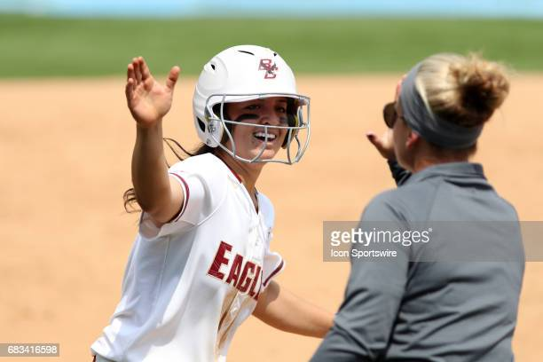 Boston College's Chloe Sharabba slaps hands with head coach Ashley Obrest as she rounds third base after hitting a home run The Boston College Eagles...
