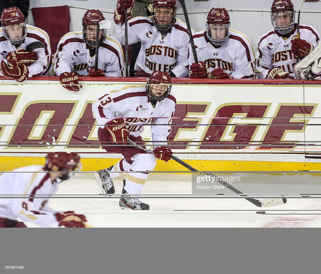 Boston College's Johnny Gaudreau (#13) skates past the Boston College bench during a hockey game between Boston College and the University of Vermont at Conte Forum in Chestnut Hill.