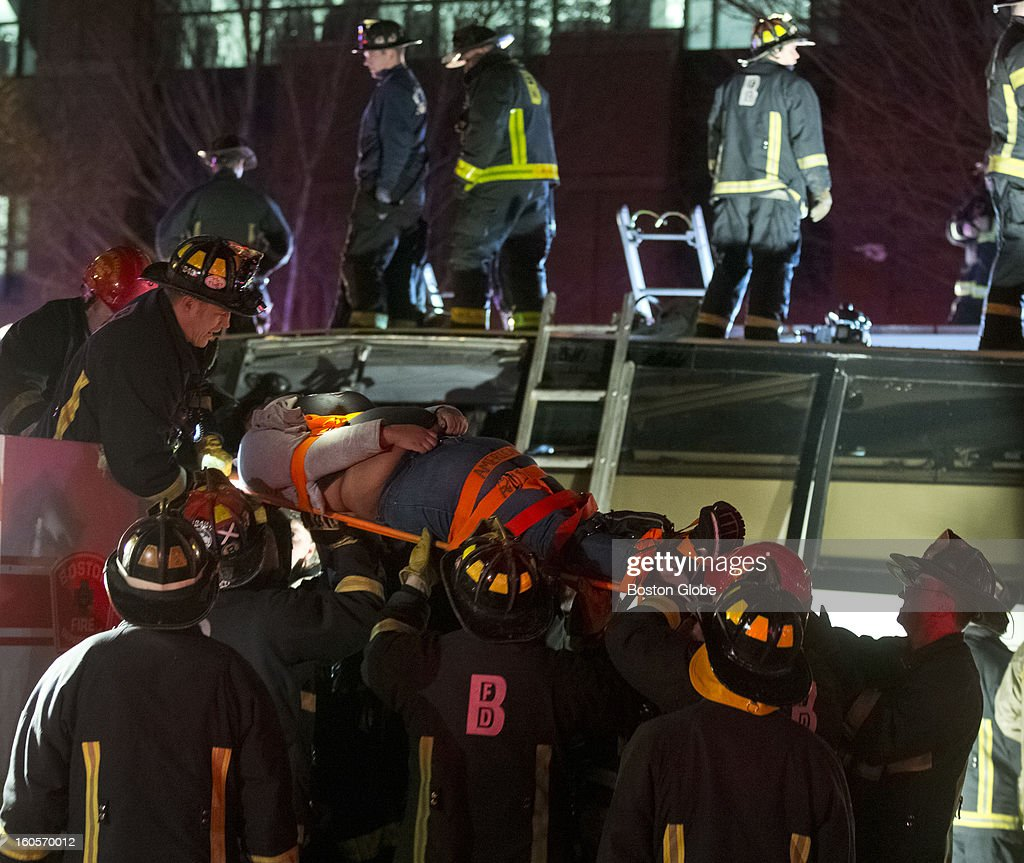 Boston Fire and Emergency personnel rescue an injured passenger on a bus that crashed under the Western Avenue Bridge on Soldiers Field Road on Saturday, Feb. 2, 2013. High school students and their adult chaperones with the Bristol, Pa.-based Destined for a Dream Foundation group were on a charter bus after a visit to Harvard University when the oversized bus crashed into a bridge. More than 30 people were injured.