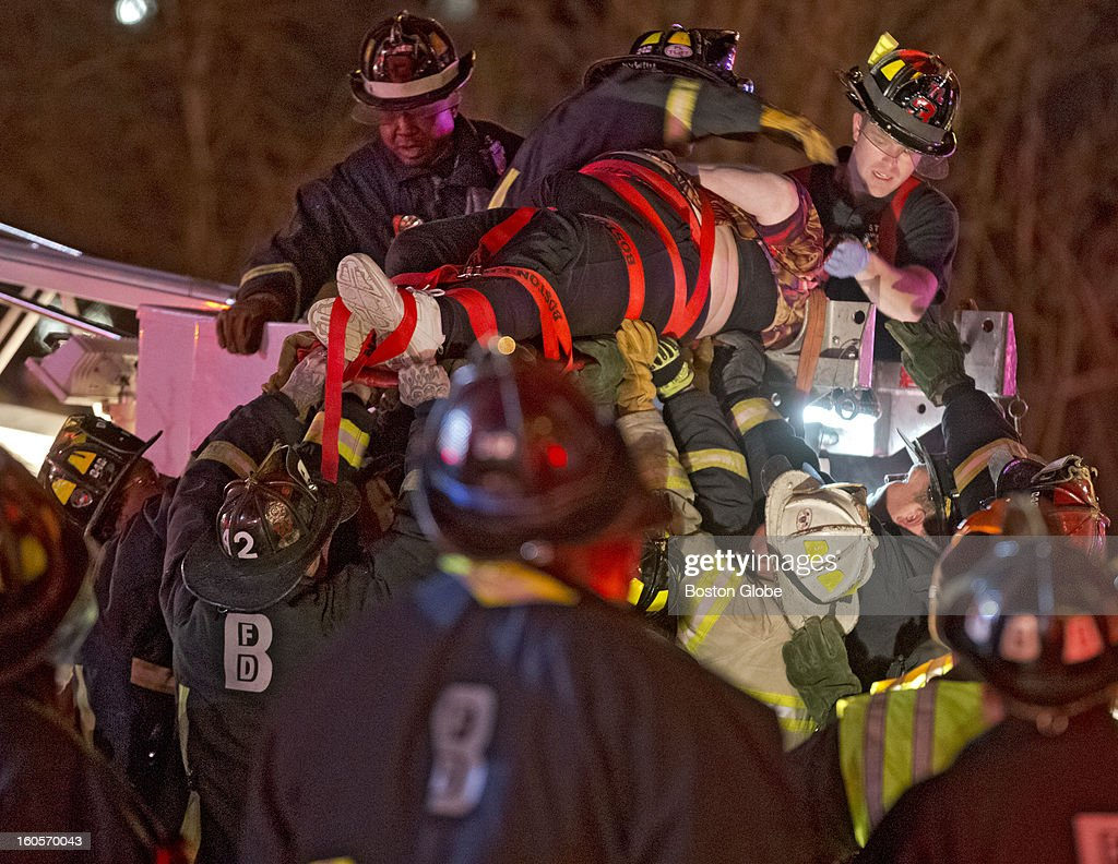 Boston Fire and Emergency personnel rescue an injured passenger on a bus that crashed driving under the Western Avenue Bridge on Soldiers Field Road on Saturday, Feb. 2, 2013. High school students and their adult chaperones with the Bristol, Pa.-based Destined for a Dream Foundation group were on a charter bus after a visit to Harvard University when the oversized bus crashed into a bridge. More than 30 people were injured.
