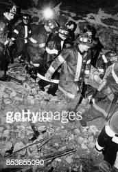 Boston Firefighters carry an injured firefighter from the scene of a threealarm fire in the Roxbury neighborhood of Boston Oct 23 1976 Firefighter...