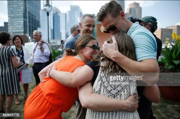Boston Marathon bombing survivors Jessica Downes left and Patrick Downes right embrace fellow bombing survivor Jane Richard as her father Bill looks...