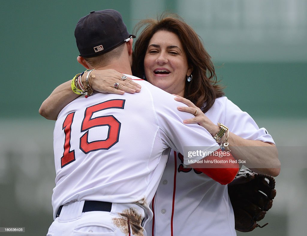 Boston Marathon bombing victim Celeste Corcoran receives a hug from Dustin Pedroia #15 of the Boston Red Sox after throwing out a ceremonial first pitch during on September 14, 2013 at Fenway Park in Boston Massachusetts.