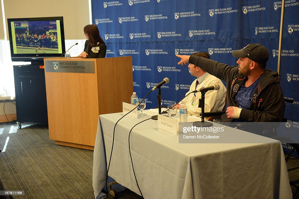 Boston Marathon bombing victim Jarrod Clowery of Stoneham, Massachusetts, describes his ordeal by pointing to a photo taken moments before the second explosion went off during a press conference at Brigham and Women's Hospital April 30, 2013 in Boston, Massachusetts. Clowery was watching the marathon with a group of friends when the second bomb went off, burning his back, arms, and legs, and embedding shrapnel into his body that was later removed by physicians.